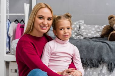 young beautiful mother and adorable daughter embracing in bedroom