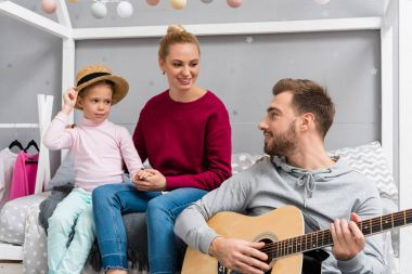 happy young father playing guitar for wife and daughter at kid bedroom