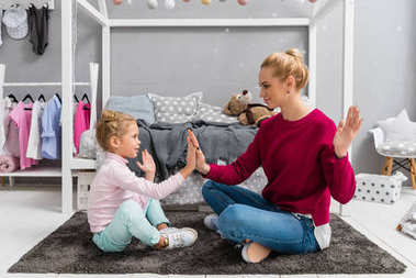 mother and daughter playing pattycake while sitting on floor