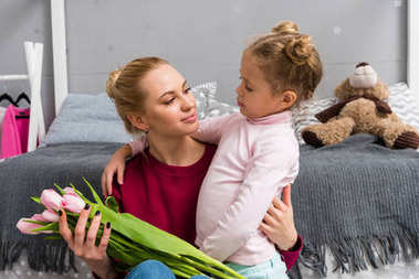 adorable little daughter presenting tulips bouquet for mother on mothers day