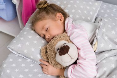 adorable little kid sleeping with teddy bear