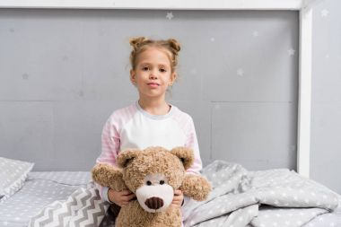 adorable little kid with teddy bear sitting on bed