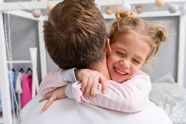 back view of happy little daughter embracing father