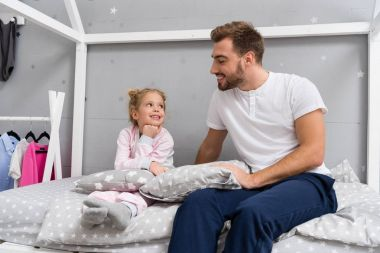 father and little daughter sitting on bed in kid bedroom