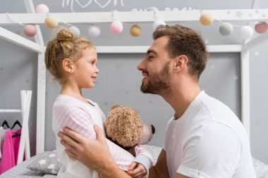 side view of young father and daughter in kid bedroom