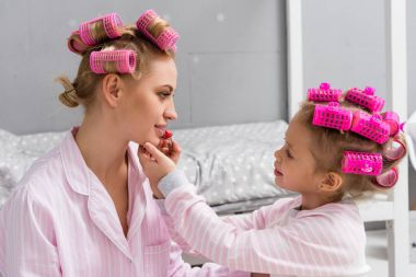 adorable daughter doing makeup applying lipstick on mothers lips