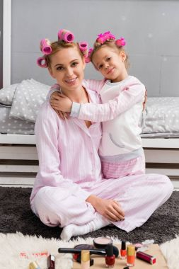 happy mother and daughter with hair rollers and in pajamas sitting on floor