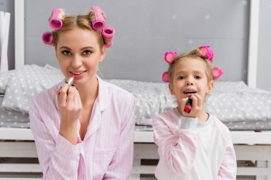smiling mother and daughter doing makeup and looking at camera