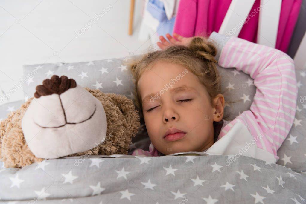 cute little kid sleeping with teddy bear