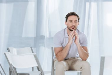 depressed middle aged man sitting on chair and looking away in empty room