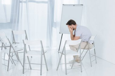 depressed middle aged man sitting on chair in empty room