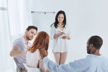psychotherapist taking notes while anonymous group supporting depressed woman