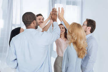 happy multiethnic middle aged people giving high five during group therapy