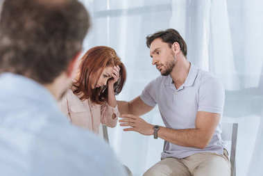 selective focus of man supporting upset middle aged woman during group therapy