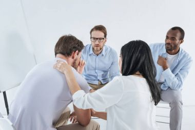 multiethnic mid adult people sitting on chairs and supporting upset man during anonymous group therapy