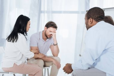 multiethnic mid adult people supporting depressed man during anonymous group therapy