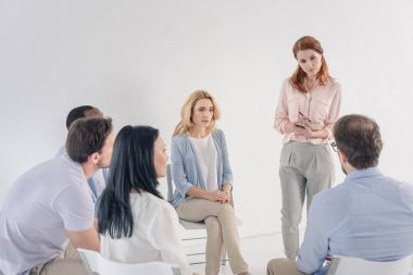 psychotherapist taking notes and working with mature multiethnic people during group therapy