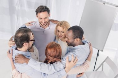 mature multiethnic people standing in circle and embracing during group therapy