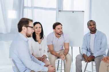 anonymous group of multiethnic middle aged people sitting on chairs during therapy