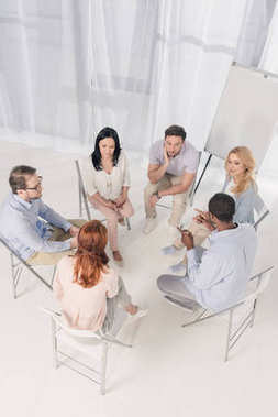 overhead view of multiethnic middle aged people sitting on chairs and talking during group therapy
