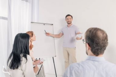 middle aged man pointing at blank whiteboard during anonymous group therapy
