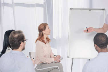 cropped shot of psychotherapist pointing at whiteboard and multiethnic people sitting on chairs during group therapy