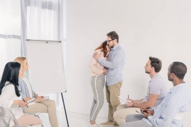 mature couple hugging while standing near blank whiteboard and other people sitting on chairs during group therapy