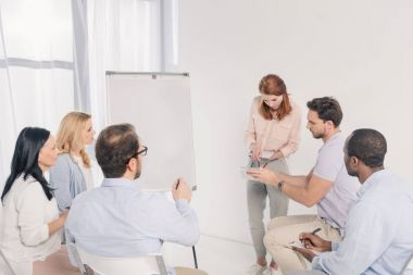 psychotherapist standing near whiteboard and talking with multiethnic people during group therapy