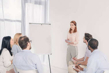 middle aged woman standing near blank whiteboard and looking at multiethnic people during group therapy