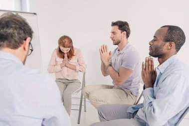 cropped shot of anonymous group praying during therapy