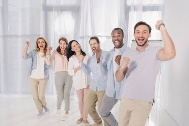 multiethnic middle aged people smiling at camera and triumphing during group therapy