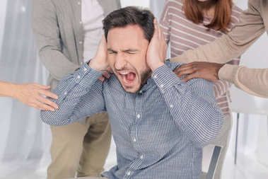 cropped shot of people supporting depressed middle aged man screaming during group therapy