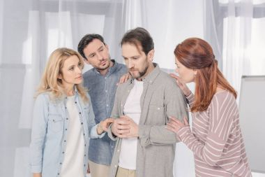 people supporting upset middle aged man during group therapy