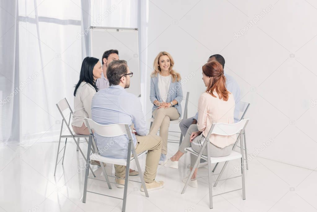 multiethnic middle aged people sitting on chairs and talking during group therapy