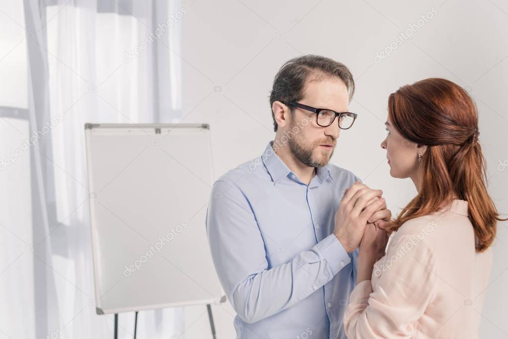 middle aged man and woman holding hands and looking at each other