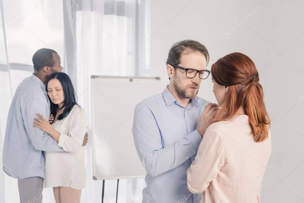 two multiethnic couples standing together and hugging during group therapy