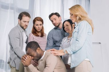 multiethnic group of people supporting upset african american man during therapy