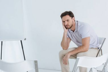depressed man sitting and looking away in empty room