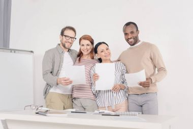 multiethnic middle aged people holding papers and smiling at camera