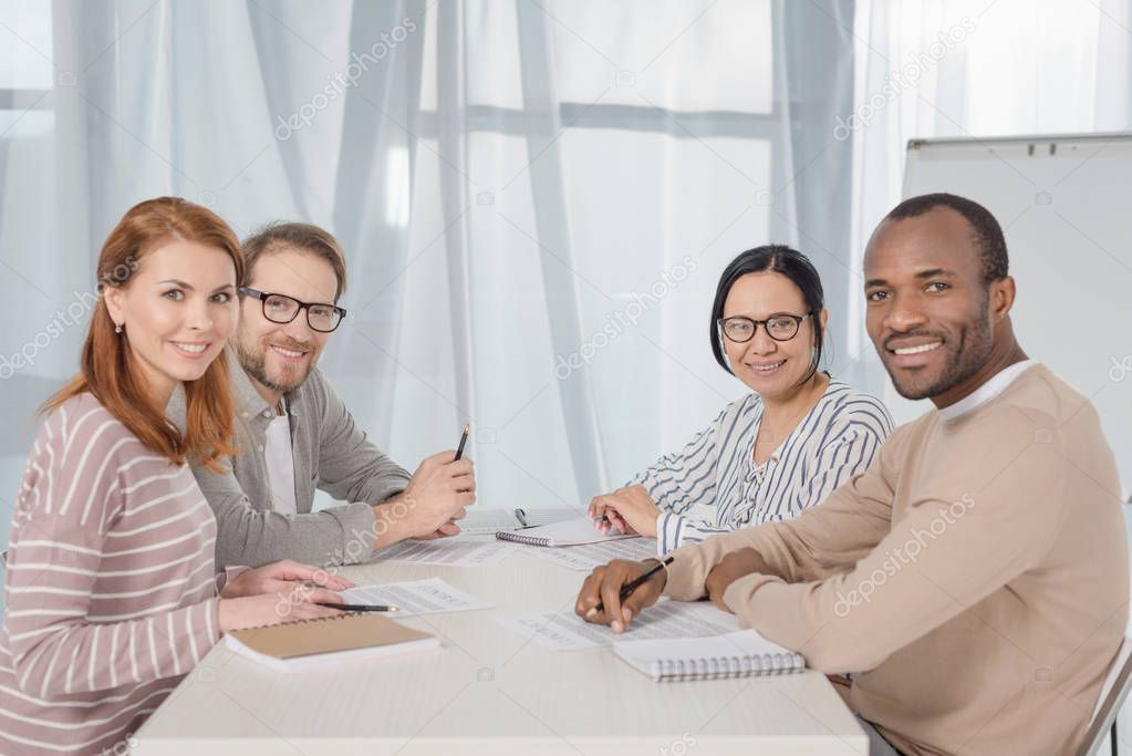 multiethnic middle aged business people smiling at camera while working together