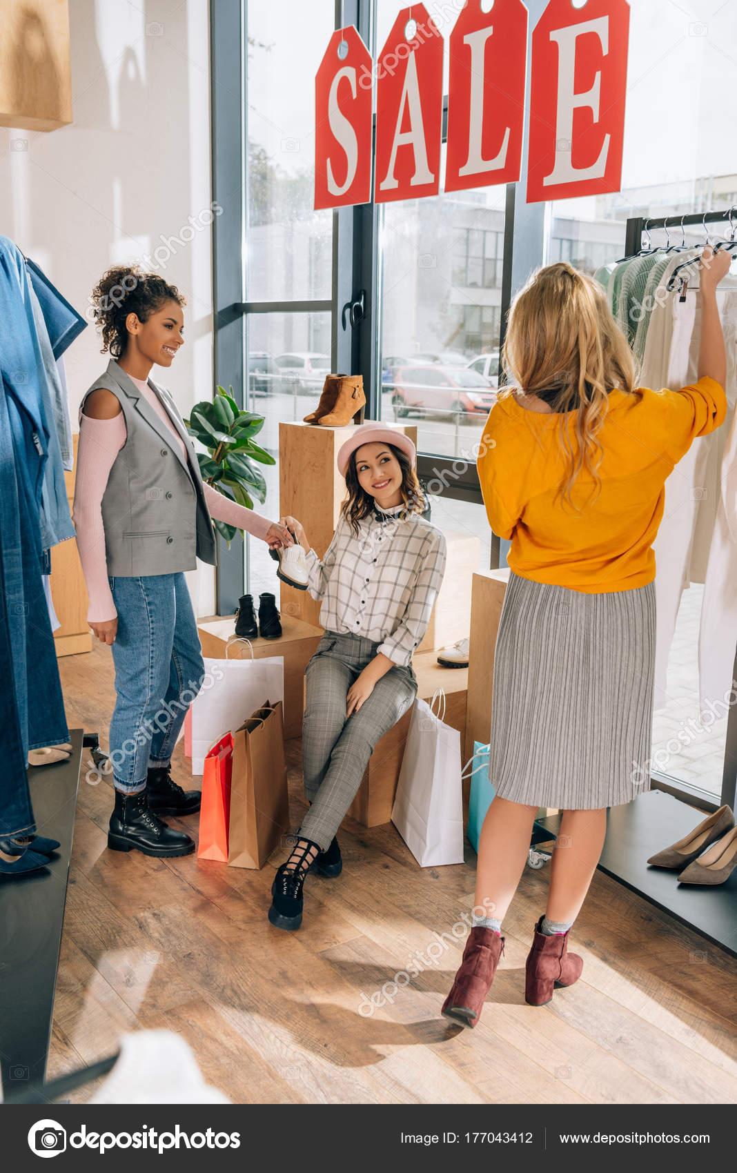 e08ceaacb36c5 Группа молодых женщин на покупки в магазине одежды Распродажа день–  Стоковое изображение