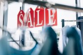 sale sign made of tags with letters on windows of boutique with hangers on foreground