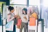 csoport fiatal nők bevásárló táskák és kávéval menni ruhaüzlet