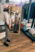 šťastná mladá žena při pohledu na zrcadlo v obchod s oblečením