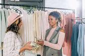 mladé stylové ženy počítání hotovosti v obchod s oblečením