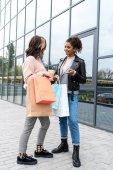 Fényképek fiatal stílusos bevásárló bimbózó a papír táskák, beszél a szabadban