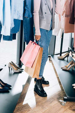 cropped shot of woman with shopping bags in clothing store