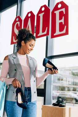 happy young woman looking for shoes at clothing store