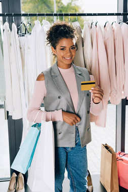 beautiful young woman showing credit card at clothing store