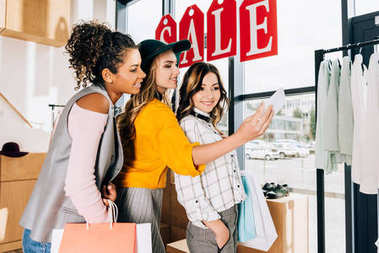 group of multiethnic young women taking selfie on shopping
